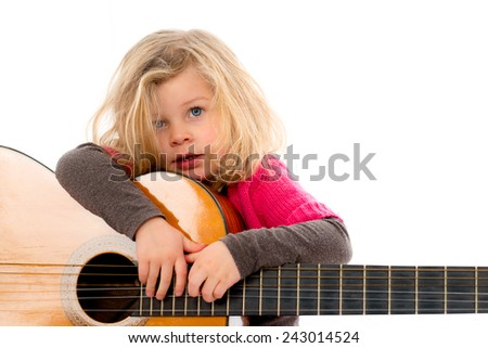 little girl is playing with a guitar - stock photo