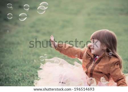 little girl is playing with bubbles in a park