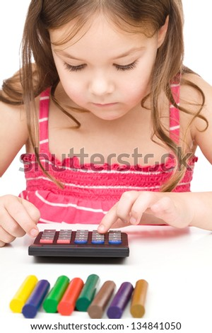 Little girl is playing with calculator, isolated over white - stock photo