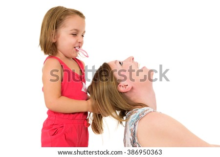 Little girl is playing with mother - fixing her hair. Both are laughing and enjoying the moment. Isolated on white.