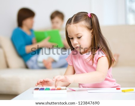 Little girl is playing with plasticine, her mother and brother at the background