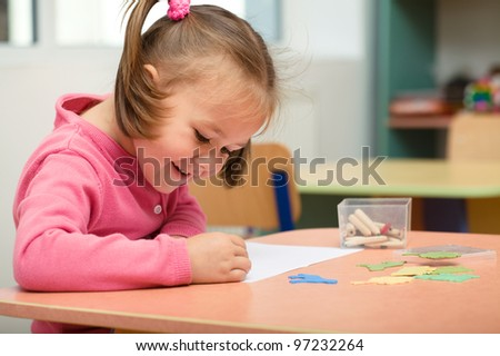 Little girl is playing with plasticine in preschool