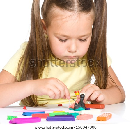 Little girl is playing with plasticine while sitting at table, isolated over white