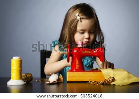 little girl is playing with sewing machine
