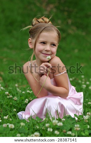 Little girl is posing on the lawn - stock photo