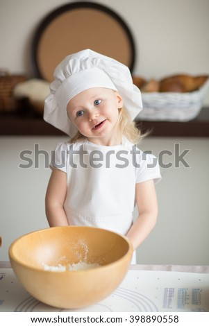 little girl is preparing a cake in a suit chef