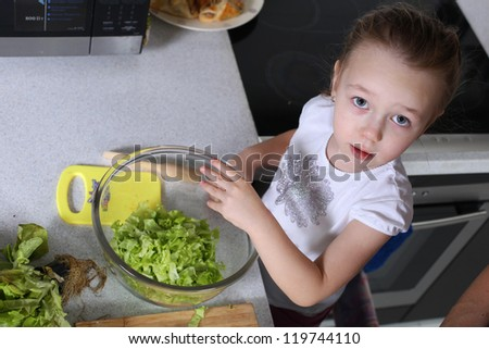 little girl is preparing salad at the table