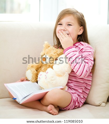 Little girl is reading a book for her teddy bears while sitting on white couch - stock photo