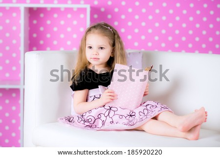 Little girl is reading a story while laying in sofa and wearing pink dress, indoor shoot - stock photo