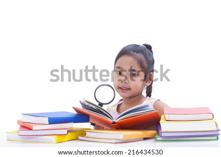 Little girl is reading book and using magnifier.