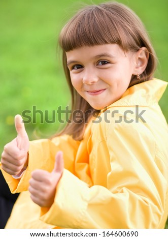 Little girl is showing thumb up gesture using both hands - stock photo