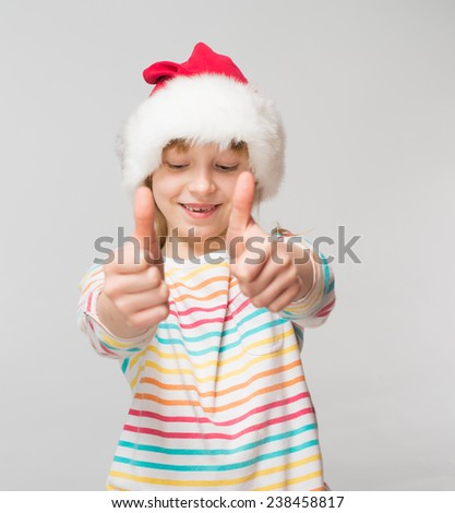 Little girl is showing thumb up sign and wearing santa hat, isolated over white