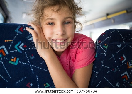 Little girl is sitting between seats in the bus. - stock photo