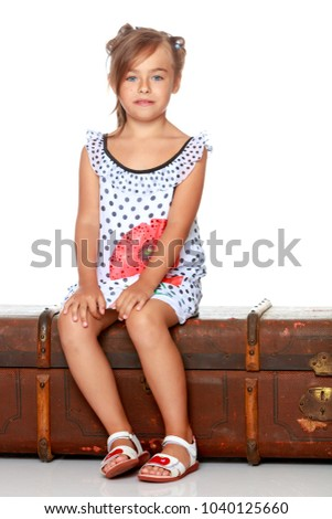 Little girl is sitting on a wooden box. Isolated on white background.