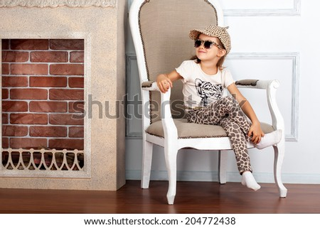 Little girl is sitting on the chair near fireplace - stock photo