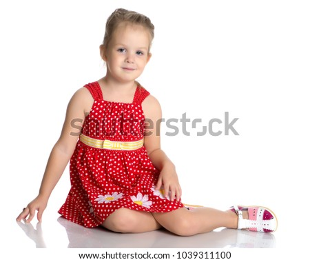 Little girl is sitting on the floor. The concept of a happy childhood. Isolated on white background.