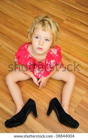 little girl is sitting on the flour, she is wearing mother's high-heels shoes, snappy dresser - stock photo