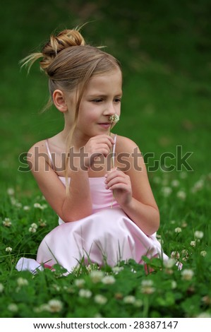 Little girl is sitting on the grass - stock photo