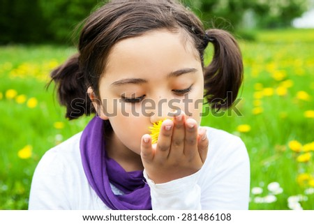 Little girl is smelling Dandelion flowers on green meadow. Child playing outdoors. Girl is happy outside and having fun. - stock photo