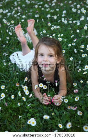 Little girl is smelling flowers while sitting on green meadow. Beautiful baby barefoot on grass - stock photo