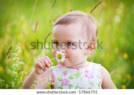 Little girl is smelling the daisy flower outdoors - stock photo