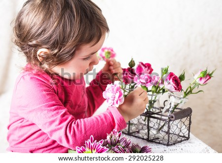 Little girl is smelling the roses. Playing the florist profession - stock photo