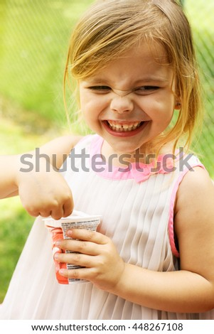Little girl is smiling and eating ice cream outside. - stock photo