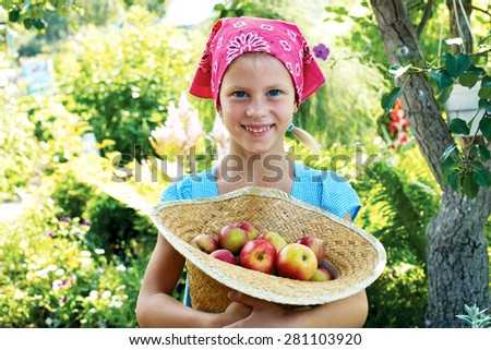 Little girl is standing with basket of apples in the apple orchard - stock photo