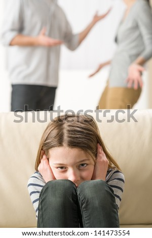 Little girl is troubled because parents arguing - stock photo