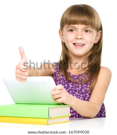 Little girl is using tablet and showing thumb up sign - stock photo