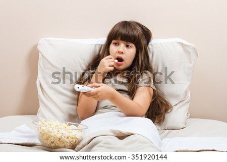 Little girl is watching tv and eating popcorn in her bed. Little girl watching tv  - stock photo
