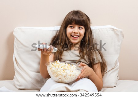 Little girl is watching tv and eating popcorn in her bed.Little girl watching tv in bed - stock photo