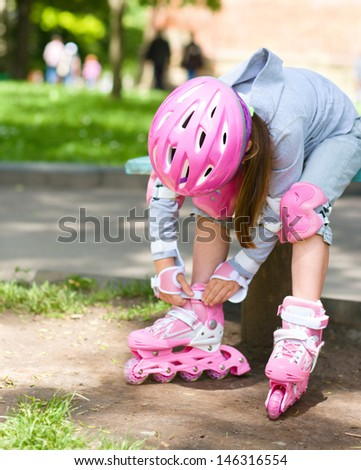 Little girl is wearing roller-blades in city park - stock photo