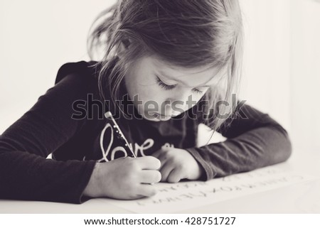 little girl is writting at the table