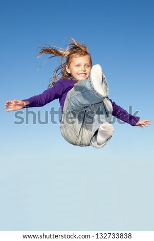 little girl jumping high in the blue sky