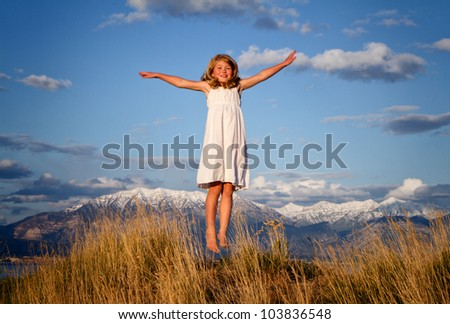 Little girl jumping in a mountain landscape with grassy foreground