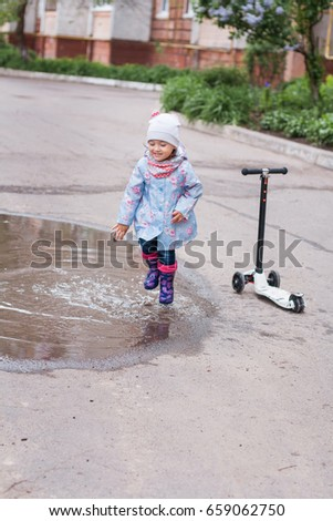Little girl jumping in muddy puddle on the road
