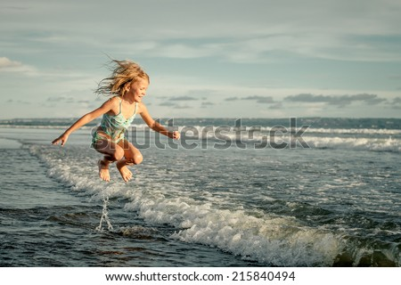 little girl  jumping on the beach on blue sea shore in summer vacation at the day time - stock photo