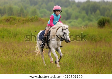 Little girl jumping on the field at a gallop Outdoors - stock photo