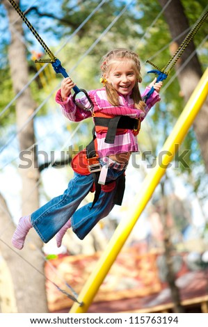 Little girl jumping on the trampoline with rubber bands - stock photo