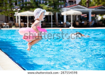 Little girl jumping to the swimming pool - stock photo