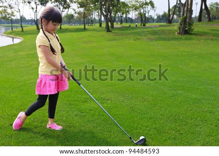 Little girl just swing golf ball on golf course fairway - stock photo