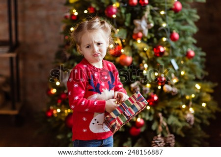 Little girl kid in the red sweater holding a gift and makes faces at Christmas background