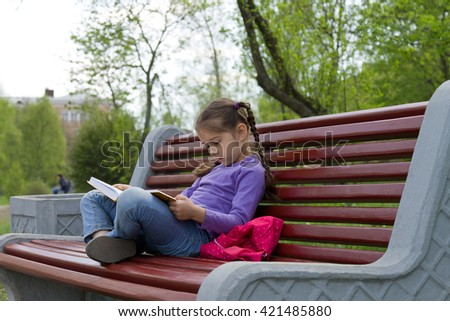 Little girl kid reading a book sitting on a bench in spring park - stock photo
