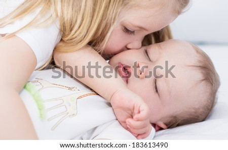 little girl kisses a sleeping baby brother on a white background - stock photo