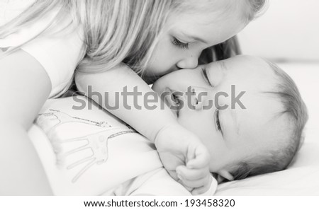 little girl kisses a sleeping baby brother on a white background ( black and white ) - stock photo
