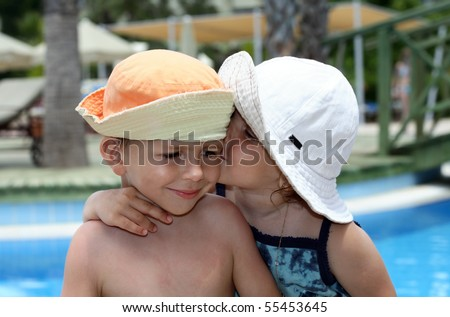 little girl kissing a boy, on pool background - stock photo