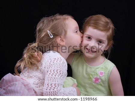 Little girl kissing her big sister - stock photo