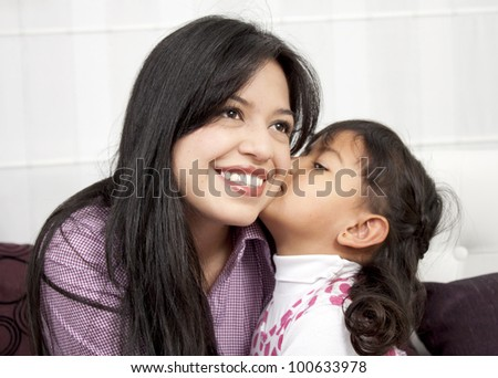 Little girl kissing her mommy in the home - stock photo