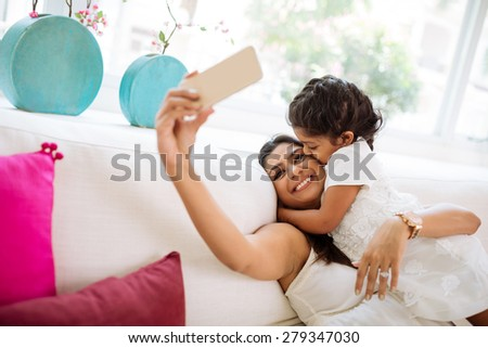 Little girl kissing her mother who is taking selfie - stock photo